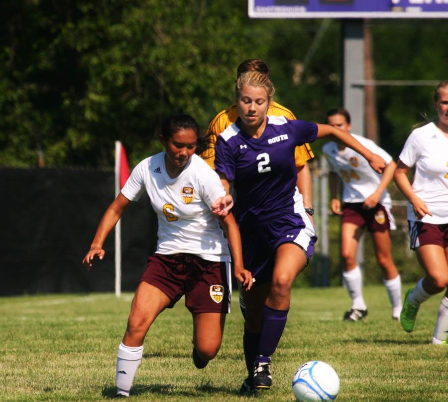 Junior Sophie Keller fights a Cougar for possession of the ball