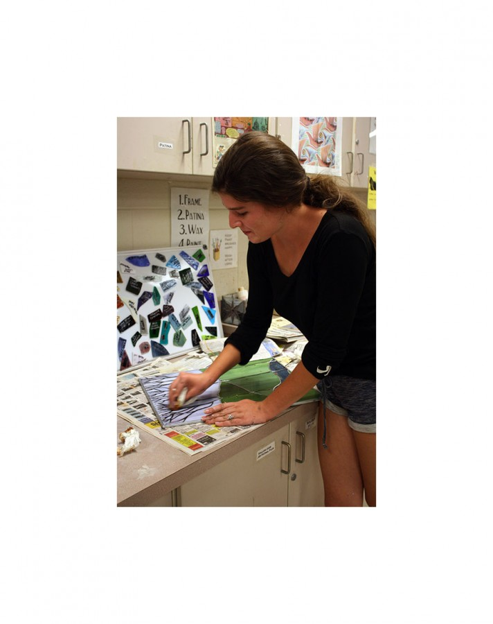 Student adds final touch to stained glass project