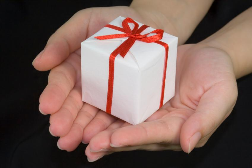 Hands+holding+a+gift+box+isolated+on+black+background