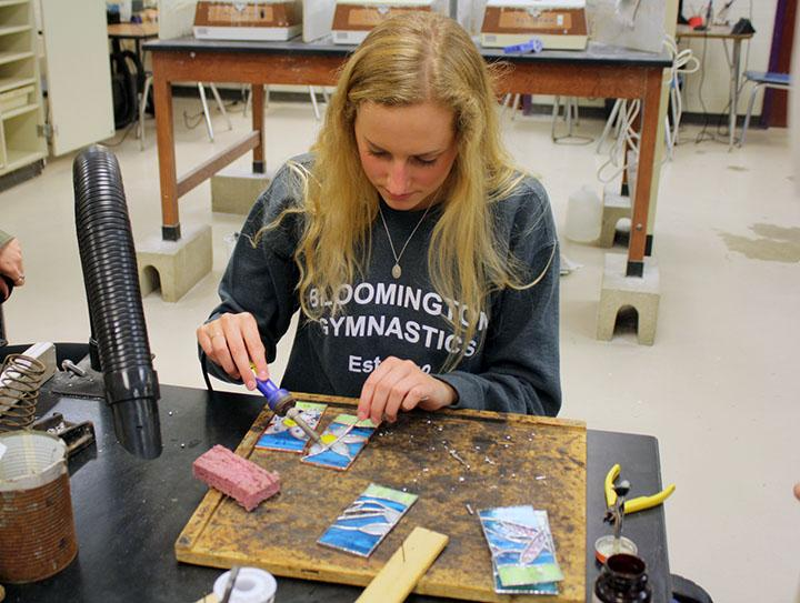 Student solders during stained glass