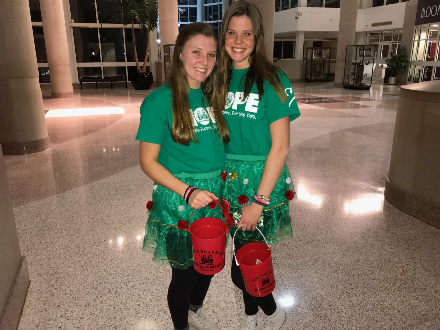 Junior execs Brittney Allen and Caroline Conrad collect admission fees for Dance Marathon's first karaoke night last night and sport matching Christmas outfits.