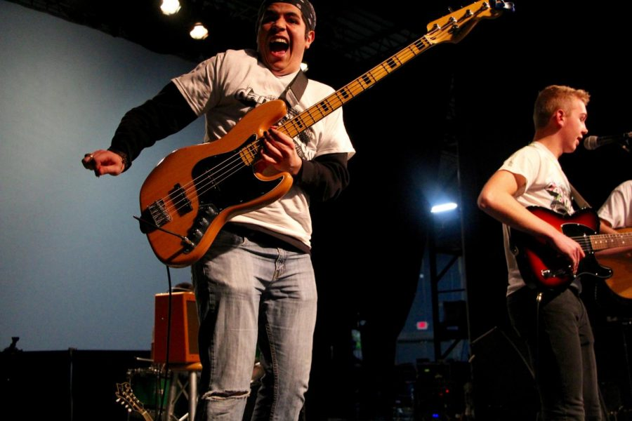 South senior and Elm Heights Band member Daniel Deckard jumps up while playing his bass guitar.