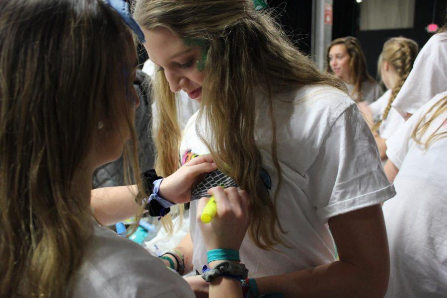 South junior Zoe Verteramo helps color South junior Riley Eurton's shirt.