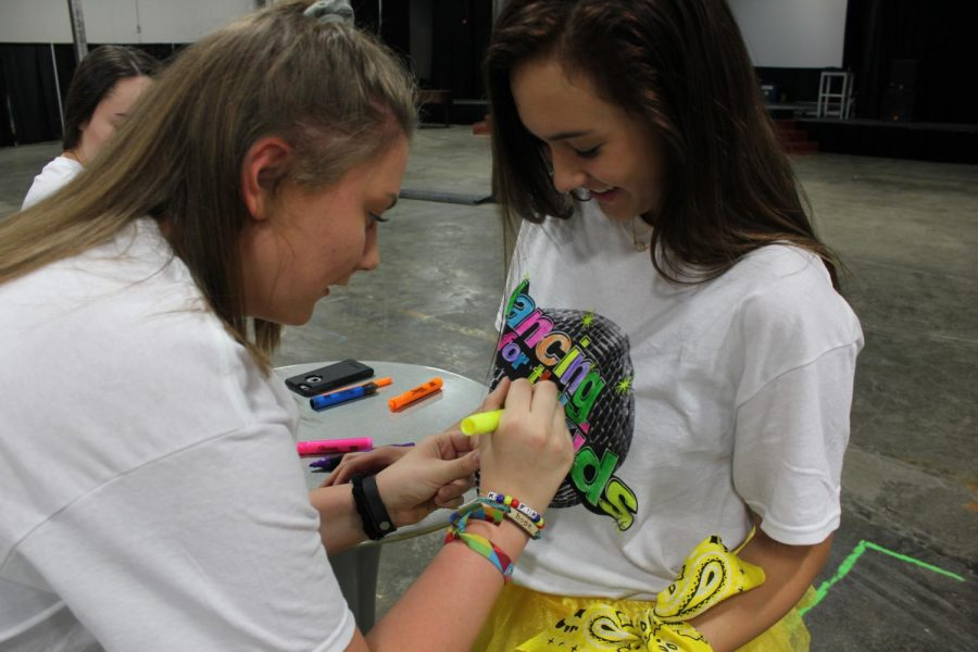 South junior Emily Doehla helps color South junior Savannah Trimble's shirt