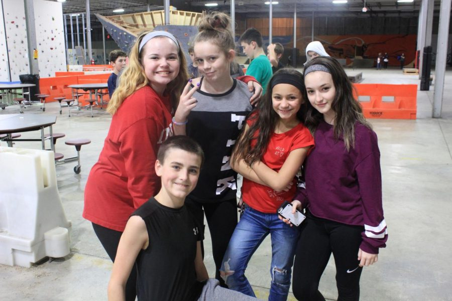 Several middle school students pose together.