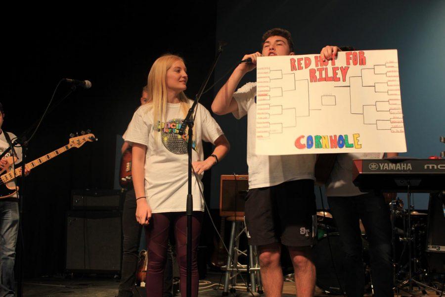 Senior Ashley Elliot and junior Calvin Prenkert announce that the cornhole tournament has begun.