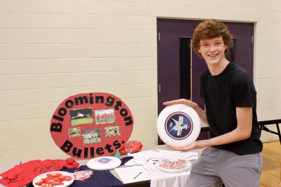 Sophomore Will Quigley poses with a frisbee in front of the Bloomington Bullets Ultimate Frisbee team booth.