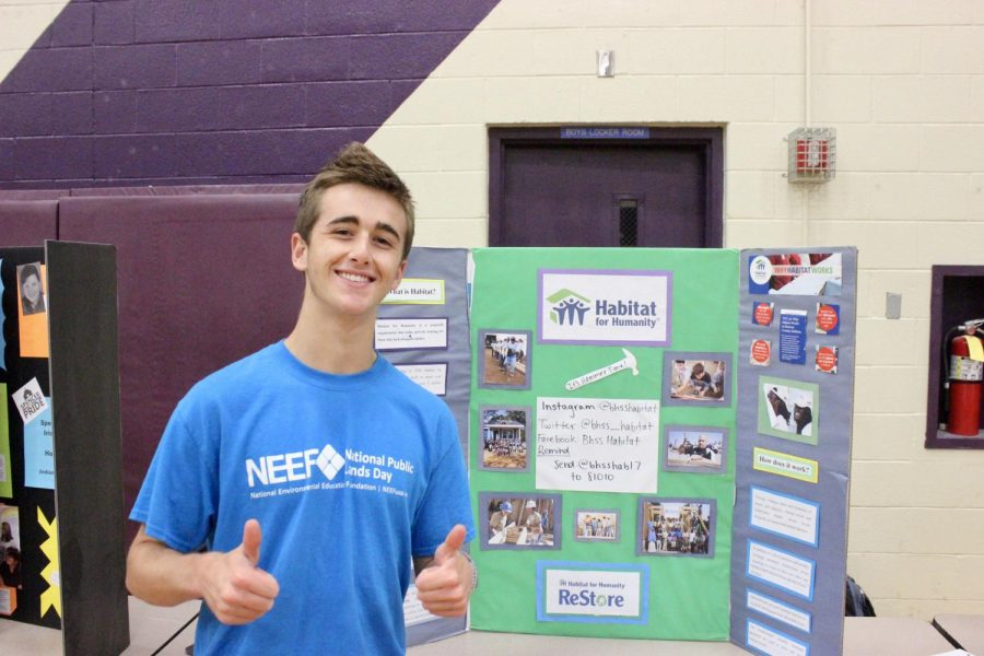 Senior Jack Foster poses in front of the Habitat for Humanity club booth.