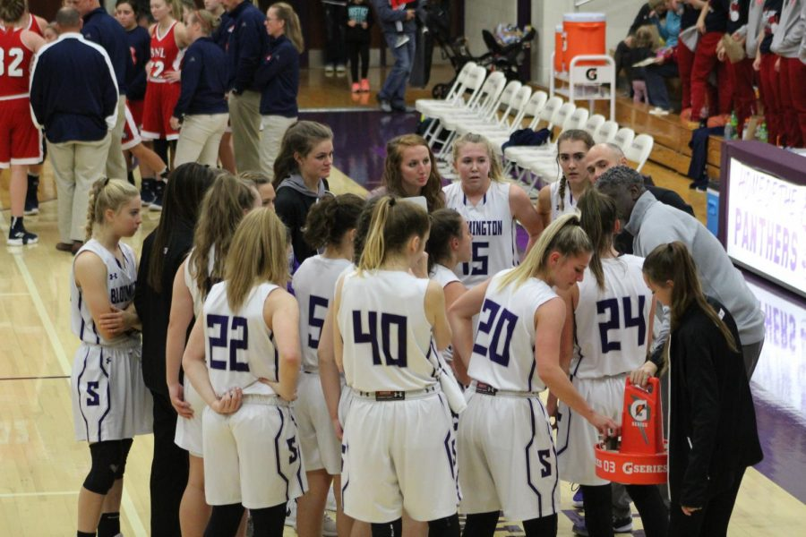 The whole team gathers during a timeout to discuss the game