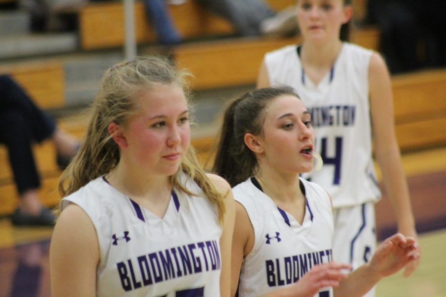 Junior Clara Voskuil (15) and senior Addy Blackwell (21) watch the team as Lauren Conner (24) walks toward them