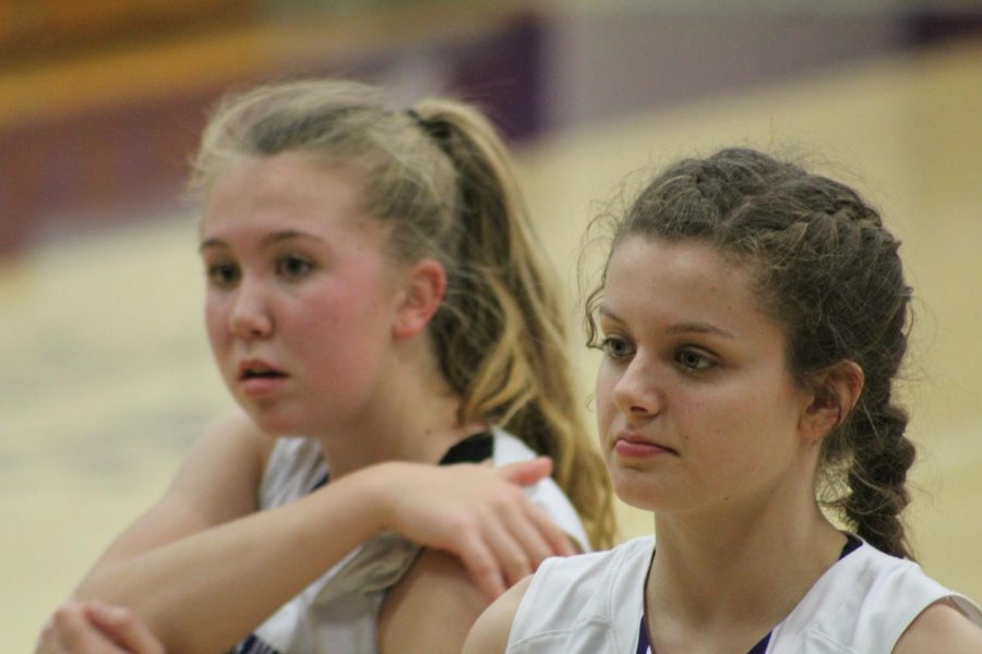 South juniors Clara Voskuil (15) and Hannah Miller (23) watch the team warm-up during half time
