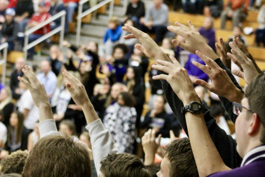 The student section hushes and raises their hands as they await a free throw from Anneke Furr (1)