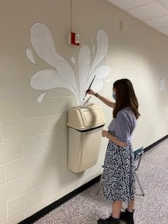 Senior Moya Stringer works on a wall painting in the B-wing. She and some other art students are spicing up a few blank walls.